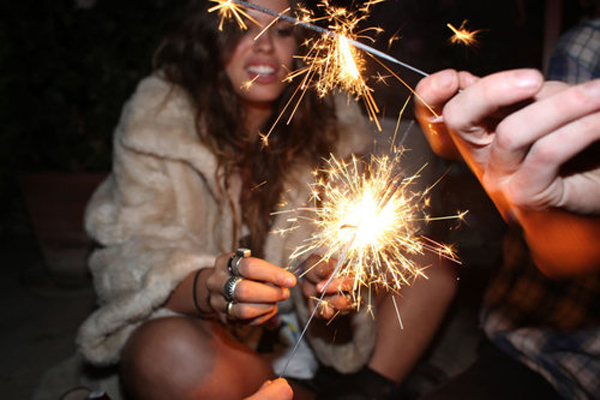 girl in fur coat with sparklers