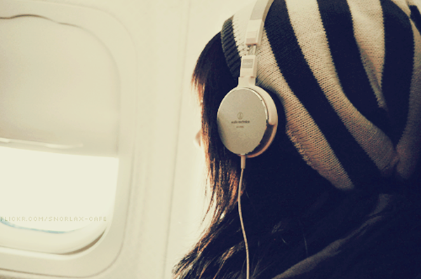 girl with headphones on a plane